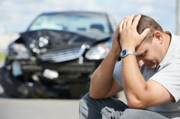 man sitting in front of crashed car holding head
